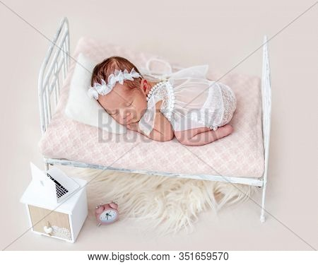 Cute asleep newborn on tiny bed with a laptop on the nightstand