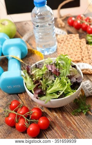 healthy lifestyle with salad, tomato, bottle of water and dumbbell