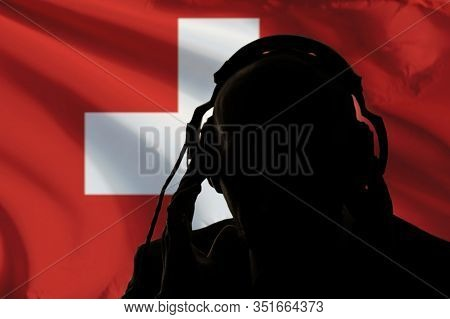 The Silhouette Of A Man With Headphones On The Background Of The Flag Of Switzerland Eavesdropping O