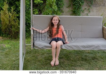 Beautiful Young Woman Swinging Outdoor. Girl On A Garden Swing. Girl 8 Or 9 Years Old On A Swing. En
