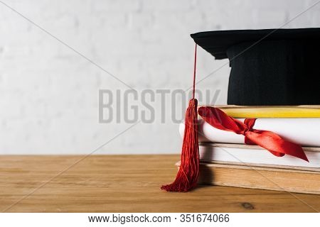 Diploma With Beautiful Bow, Graduation Cap With Red Tassel On Top Of Books On Table On White Backgro