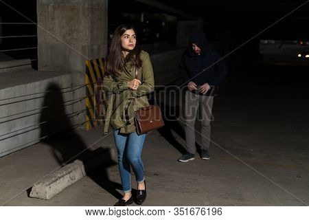 Unaware Woman Looking Away While Followed By Robber In Parking Lot At Night