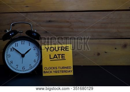 You're Late - Clocks Turned Back Yesterday Write On A Sticky Note Isolated On Wooden Background.
