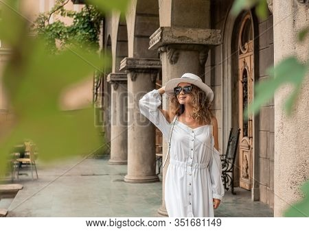 Fashion Girl Female Looking The Old City. Girl In Europe. Travel Concept. Beautiful Girl In White Dr