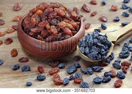 Red Raisins In A Bowl On A Wooden Table.  Black Raisins In A Spoon. Different Varieties Of Raisins