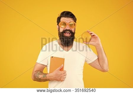 Nerd Is The New Cool. Bearded Nerd Man. Study Nerd Holding Book And Orange Fruit On Yellow Backgroun