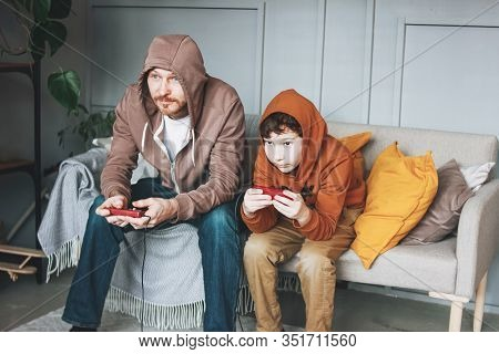 Father And Son Tween Boy In Hoodies Playing Computer Games With Joystick At The Home Tipical Caucasi