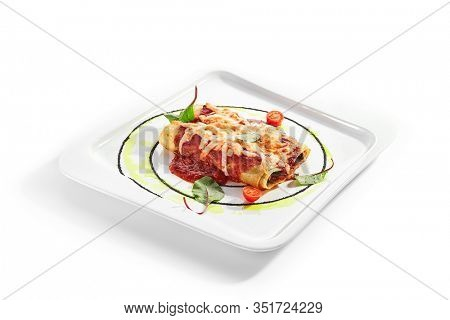 Vegetable cannelloni with dorblu cheese and tomato sauce. Rolled lasagna served with aromatic spinach. Traditional Catalan cuisine. Tasty mediterranean dish closeup view. Italian meal