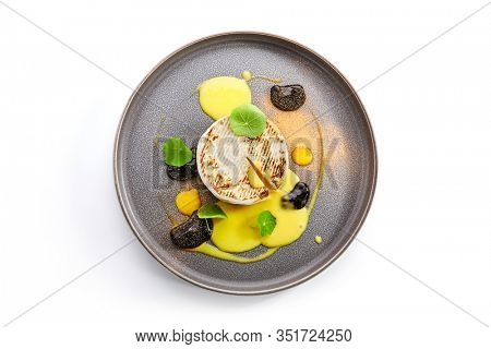 Baked Camembert in plate. Served melted cheese in white rind. Restaurant gourmet food, appetizer. French cuisine. Creamy soft cheese round chunk. Cow milk dairy product portion