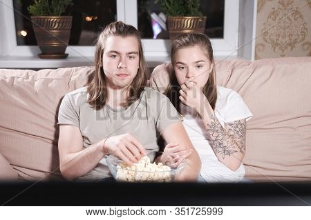 Portrait Of A Long-haired Guy And Girl With Popcorn In Their Hands On The Couch Watching Tv. Family