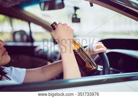 Drunk Asian Woman Drinking Alcohol While Driving Car On Road,women Drive Her Car With A Bottle Of Be