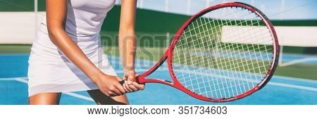 Tennis player woman in position holding red racket on outdoor blue tennis court banner panorama header for tennis classes at sports club.
