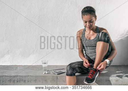 Runner woman tying running shoes laces wearing tech wearable technology smartwatch. Female athlete jogger using smart phone living a healthy active lifestyle drinking water.