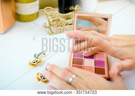Swatches Of Eye Shadows Palette On A Female Fingers. White Background. Woman Puts Swatch On Her Fing