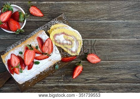 Sweet Biscuit Roll With Strawberries And Cream On A Wooden Background. Top View. Copy Space