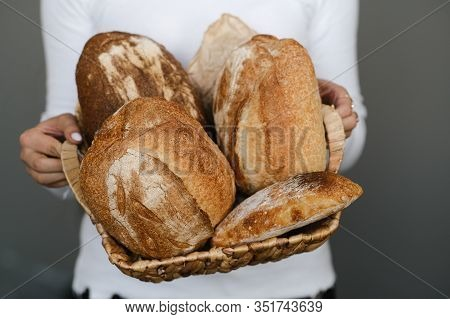 Hands Of A Baker Hold A Wicker Basket With Different Homemade Loaf Of Bread Rustic. Bakery Employee