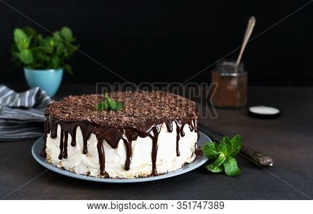 Vanilla Cake With Chocolate Icing, Chocolate Chips And Mint On A Dark Background.