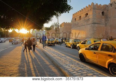 Sfax, Tunisia - December 22, 2019: The Impressive Ramparts Of The Medina With A Taxi Stand At Sunset