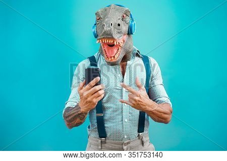 Tattooed Man With T-rex Mask Using Smartphone While Listening Music - Crazy Senior Guy Choosing Play