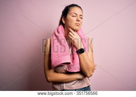 Young beautiful brunette sportswoman wearing sportswear and towel over pink background Touching painful neck, sore throat for flu, clod and infection