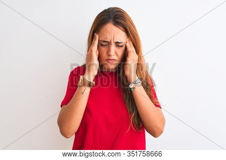 Young redhead woman wearing red casual t-shirt stading over white isolated background with hand on head for pain in head because stress. Suffering migraine.