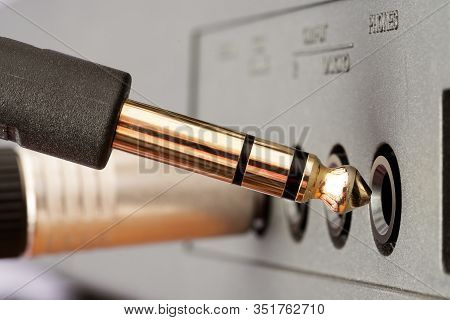 Closeup Of Golden Trs Phone Jack Audio Connector Being Plugged Into Socket On Audio Device. Music, A