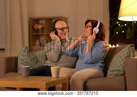 technology, old age and people concept - happy senior couple with headphones listening to music at home in evening
