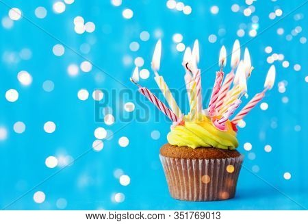 holiday, celebration, greeting and party concept - birthday cupcake with buttercream frosting and many burning candles over festive lights on blue background