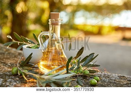Olive oil and olive berries with leaves outdoor