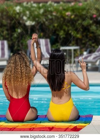 Vertical Photo Of Two Girls From Different Ethnic Groups Sitting On An Lgtb Flag At The Edge Of The