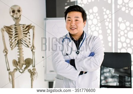 Portrait Of Friendly Asian Korean Doctor Man At His Office Smiling To Camera. Young Smiling Clinicia