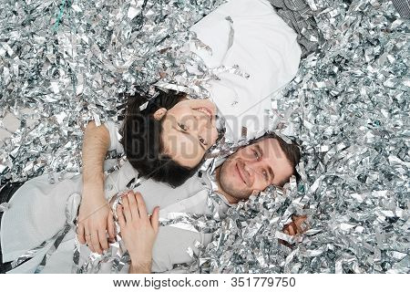 Cheerful Teenagers Wallow In Tinsel. The Girl And The Guy Are Smiling And Having Fun In A Festive Co