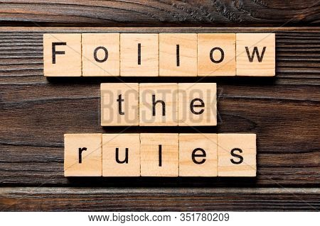 Follow The Rules Word Written On Wood Block. Follow The Rules Text On Table, Concept
