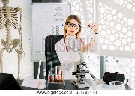 Beautiful Woman Scientific Researcher Or Doctor Holding A Liquid Solution In Flask. Attractive Young