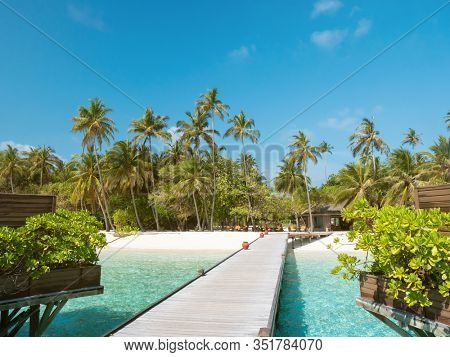 Tropical Island with Palm Trees and Wooden Pier in Indian Ocean on Maldives. Sunny Day. Tropical Beach with Water Bungalows on Maldives.