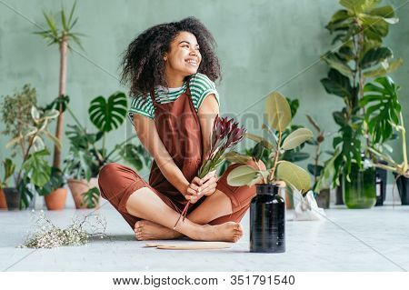 Mixed Race Playfu Woman Sitting On Floor Gardening In Home. Growing Plants At Home. Plant Parent Con
