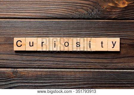Curiosity Word Written On Wood Block. Curiosity Text On Table, Concept