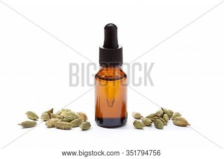 Cardamom Essential Oil In Amber Bottle Isolated On White Background. Elettaria Cardamomum Oil