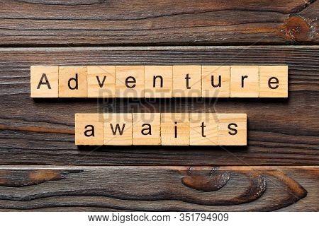 Adventure Awaits Word Written On Wood Block. Adventure Awaits Text On Wooden Table For Your Desing,