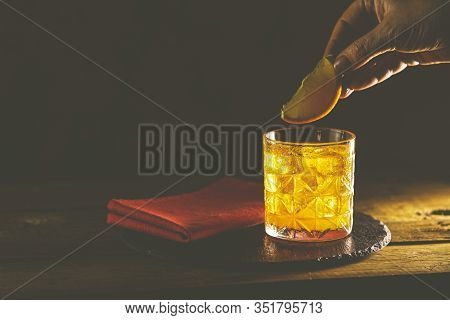 Woman Hand Decorate Orange Slice Alcoholic Cocktail Negroni Of The Glass. Drink With Gin, Campari Ma