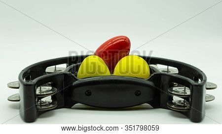 Black Tambourine With Eggs Shakers On Top On A White Background With Space At The Top Of The Image.