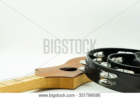 Black Tambourine On A Four-stringed Wooden Guitar On A White Background. Acoustic Instrument Concept