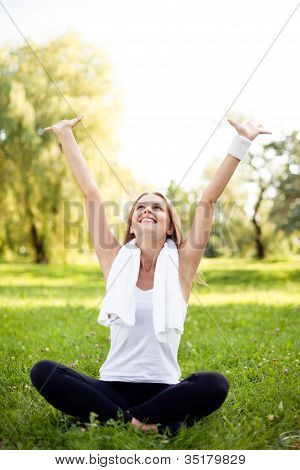 Pretty Young Woman With Arms Raised Sitting In Park