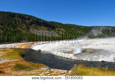 Black Sand Basin With Cliff Geyser Erupting At Yellowstone National Park.