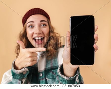 Photo of nice delighted woman in knit hat showing and pointing finger at cellphone isolated over beige background