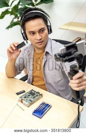 asian male IT vlogger and blogger live Technology upgrand on laptop memory ram using mobile phone recording live vlog video. Online influcencer on social media concept.