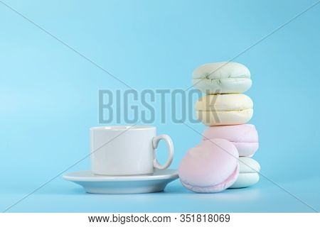 Air Marshmallows In Pastel Shades With Cup Tea. A Gentle Marshmallows. A Gentle Zephyr On A Blue Bac