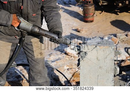 Demolition Of Rebots At The Construction Site. Builder With Hammer Breaking Pills. Demolition With A
