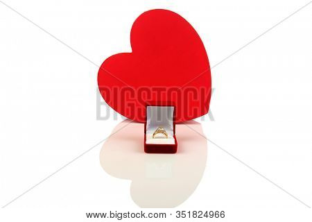 Engagement Ring. Valentines Day Gift. Wedding Ring. Red Heart with an Diamond Engagement Ring. Isolated on white. Clipping path. Room for text. Will you marry me? Love is in the air.