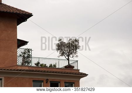 Balcony Projecting From Building Wall. Italian Balcony With Flowering Plants And Flowerpots. Balcony
